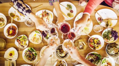 Top view wine pairing cheering glasses over middle eastern food