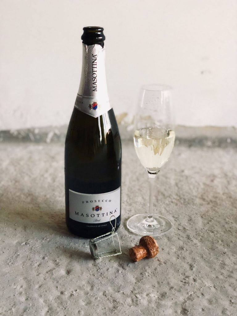 A glass and bottle of prosecco